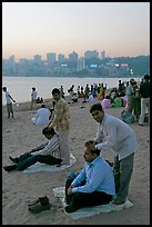 Head masseurs and Mumbai skyline at sunset,  Chowpatty Beach. Mumbai, Maharashtra, India ( color)