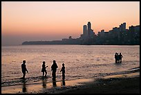 People standing in water at sunset with skyline behind, Chowpatty Beach. Mumbai, Maharashtra, India ( color)