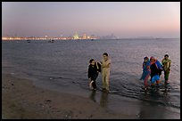 Women walking in water by night, Chowpatty Beach. Mumbai, Maharashtra, India ( color)