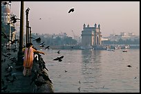 Woman feeding birds, with Gateway of India in background, early morning. Mumbai, Maharashtra, India