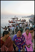 Women sitting on waterfront with boats behind at twilight. Mumbai, Maharashtra, India ( color)