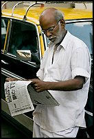 Man reading newspaper next to taxi. Mumbai, Maharashtra, India ( color)