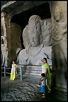 Woman and children standing in front of Mahesh Murti, main  Elephanta cave. Mumbai, Maharashtra, India ( color)