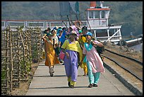 Women walking on  jetty, Elephanta Island. Mumbai, Maharashtra, India ( color)