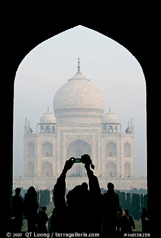 Tourist pointing  digital camera to Maj Mahal, framed by arch of gateway. Agra, Uttar Pradesh, India