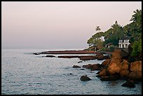 Boulders, beachfront house, and palm trees at sunrise. Goa, India ( color)