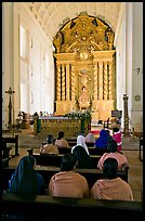 Indian women sitting in front of the altar, Basilica of Bom Jesus, Old Goa. Goa, India