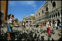 Tourists feeding  pigeons, Piazzetta San Marco (Square Saint Mark), mid-day. Venice, Veneto, Italy