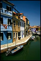Canal surrounded by houses painted  a multitude of bright colors, Burano. Venice, Veneto, Italy