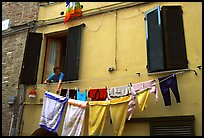 Woman hanging laundry. Siena, Tuscany, Italy ( color)