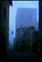Street and medieval tower at dawn in the fog. San Gimignano, Tuscany, Italy
