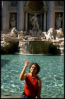 Tourist tosses a coin over her shoulder in the Trevi Fountain. Rome, Lazio, Italy ( color)