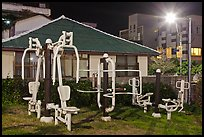 Exercise equipment in yard at night, Seogwipo. Jeju Island, South Korea (color)