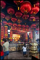 Woman in prayer, altar and lanters, Kuan Yin Teng temple. George Town, Penang, Malaysia ( color)