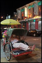 Driver taking nap in trishaw at night. George Town, Penang, Malaysia (color)