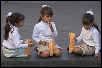 Three little girls in school uniform eating snack. Guadalajara, Jalisco, Mexico (color)