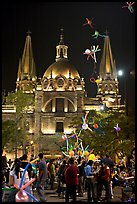 Children play with inflated balloons behind the Cathedral by night. Guadalajara, Jalisco, Mexico