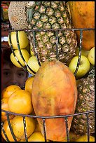 Boy peers from behind fruits offered at a juice stand, Tlaquepaque. Jalisco, Mexico ( color)