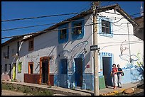 Two women outside of corner house with colorful door and window outlines, Puerto Vallarta, Jalisco. Jalisco, Mexico
