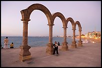 Boy standing by the Malecon arches at dusk, Puerto Vallarta, Jalisco. Jalisco, Mexico ( color)