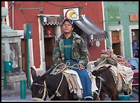 Young man riding a donkey in the streets. Guanajuato, Mexico