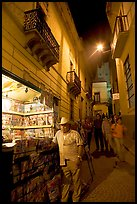 Man at a Newstand booth in a narrow callejone at night. Guanajuato, Mexico