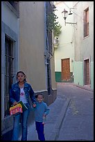 Woman and child walking in a narrow street. Guanajuato, Mexico (color)