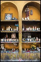 Candles, flowers, and religious offerings in a roadside chapel. Mexico