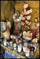 Religious figures and candles in roadside chapel. Mexico