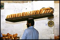 Man carrying many loafes of bread on his head. Jerusalem, Israel (color)