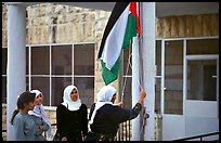 Women raise the Palestian flag at a school in East Jerusalem. Jerusalem, Israel (color)