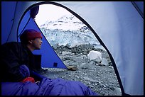 Visitor in  tent looking outside to Lamplugh Glacier. Glacier Bay National Park, Alaska