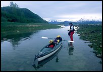 Kayaker tows kayak into a shallow tidal channel into Scidmore Bay. Glacier Bay National Park, Alaska