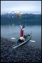 Kayaker unloading the kayak by throwing stuff sacks out. Glacier Bay National Park, Alaska (color)