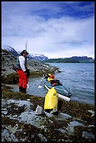 Kayaker standing next to dry bag and kayak on a small island in Muir Inlet. Glacier Bay National Park, Alaska