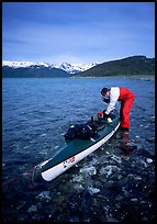 Kayaker tying up gear on top of the kayak,  East Arm. Glacier Bay National Park, Alaska