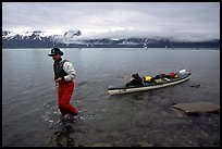 Kayaker towing kayak, East arm. Glacier Bay National Park, Alaska (color)