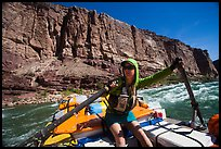 Woman stirring raft with oars in rapid. Grand Canyon National Park, Arizona