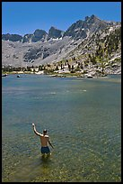 Man standing in alpine lake, lower Dusy Basin. Kings Canyon National Park, California