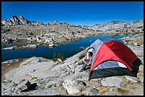 Man sitting in tent above lake, Dusy Basin. Kings Canyon National Park, California