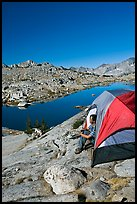 Man looking out from tent above lake, morning, Dusy Basin. Kings Canyon National Park, California
