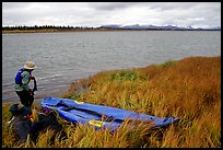 Canoeist deflating the canoe. Kobuk Valley National Park, Alaska (color)