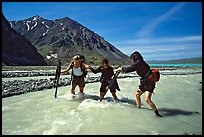 Hikers crossing a stream next to Lake Turquoise. Lake Clark National Park, Alaska
