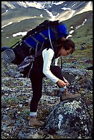 Woman backpacker with a large backpack tying up her shoelaces. Lake Clark National Park, Alaska