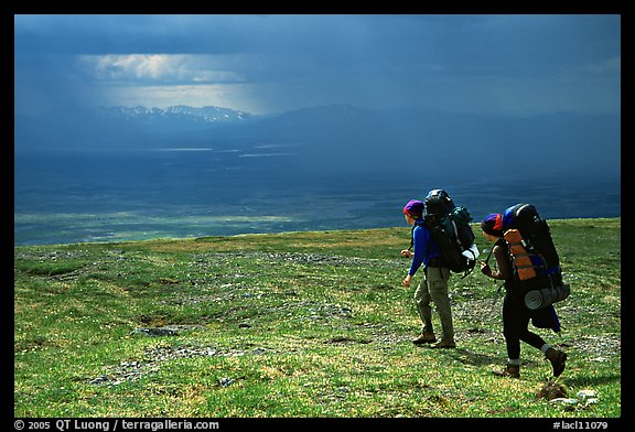 Two backpackers arrive at a ridge as a storm clears. Lake Clark National Park, Alaska