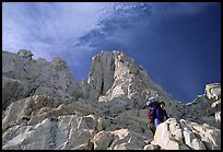 Looking up to woman scrambling on rocks on the East face of Mt Whitney. Sequoia National Park, California (color)