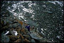 Backpacker in boulder field at the base of the Arrigetch Peaks. Gates of the Arctic National Park, Alaska