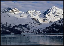 Coastal mountains with glacier dropping into icy fjord. Glacier Bay National Park, Alaska, USA. (color)