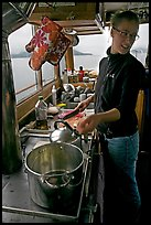 Chef cooking aboard small boat. Glacier Bay National Park ( color)