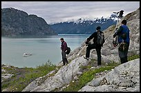 Film crew carrying a motion picture camera down rocky slopes. Glacier Bay National Park, Alaska, USA. (color)